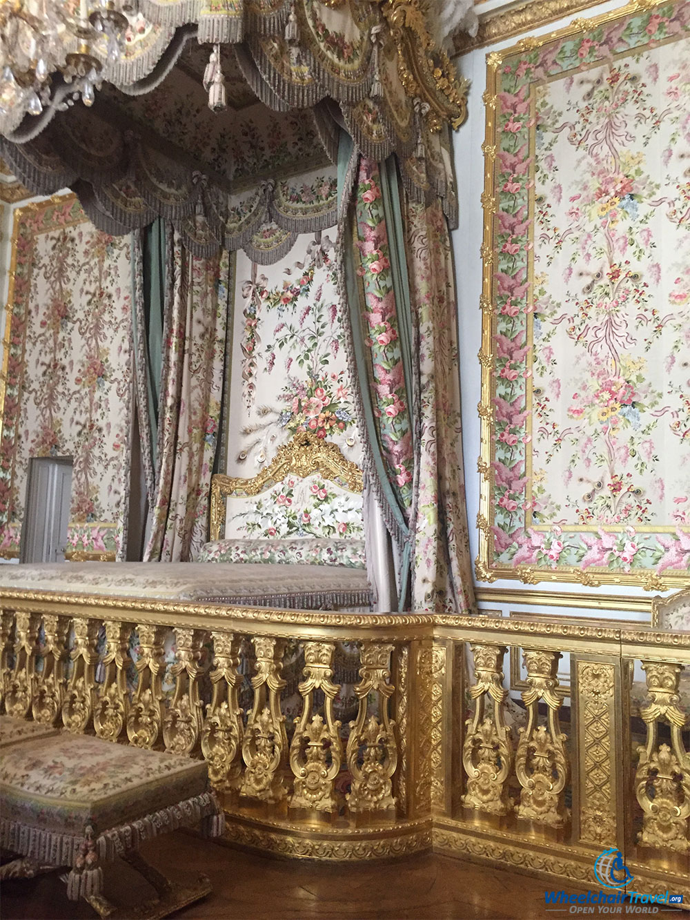 PHOTO DESCRIPTION: Bed with floral drapes extending from the ceiling.
