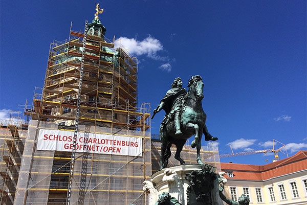 PHOTO DESCRIPTION: Cupola Dome of Charlottenburg Palace covered in scaffolding and under construction, with the statue of Friedrich Wilhelm I seen in foreground.