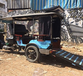 PHOTO DESCRIPTION: Mobilituk wheelchair accessible tuk-tuk with its ramp extended out onto the ground.