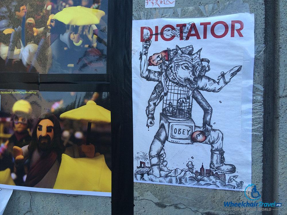 PHOTO DESCRIPTION: Political cartoons on a Harcourt Road median wall in Hong Kong.