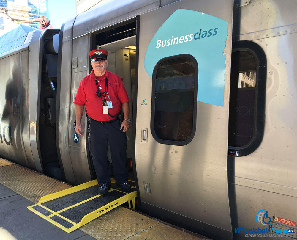 PHOTO: Wheelchair boarding ramp between platform and Acela train, with train conductor in frame.