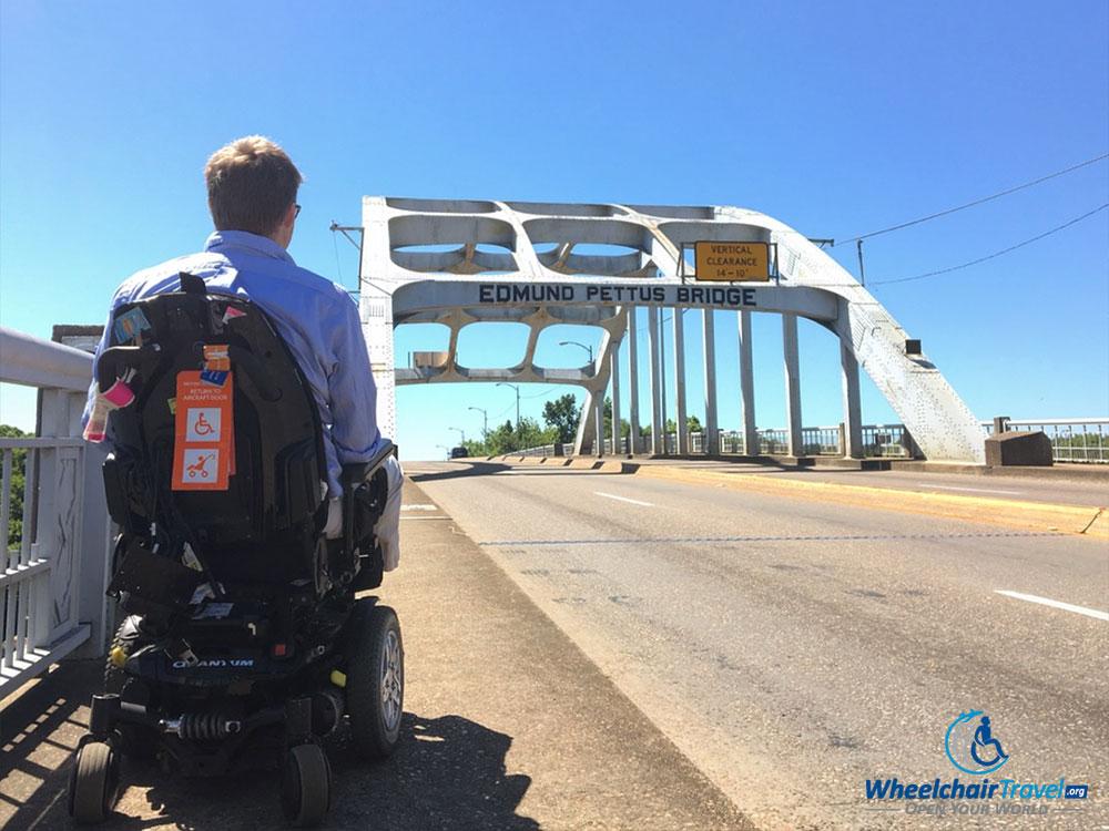 John Morris, in a wheelchair, looking towards the Edmund Pettus Bridge
