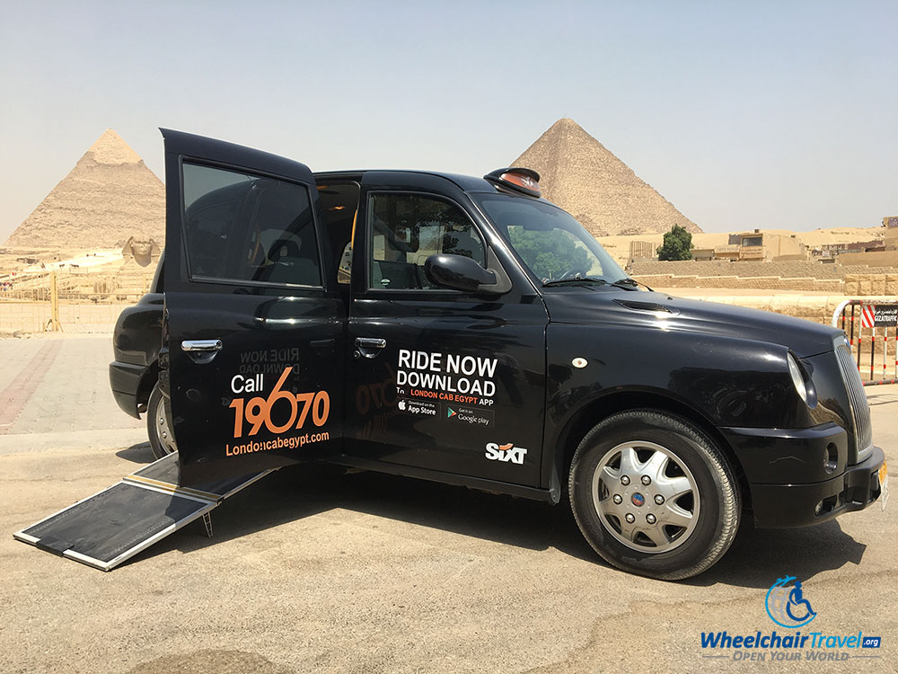 London Cab with wheelchair ramp extended in front of the Pyramids of Giza
