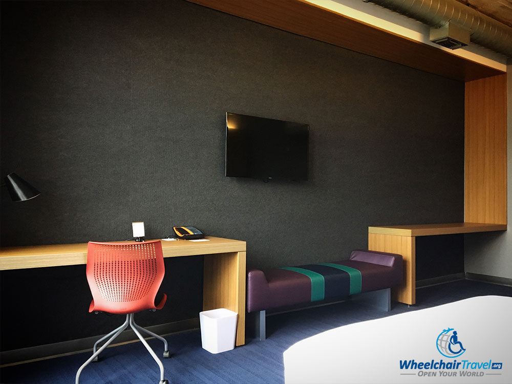 Wall-mounted television, desk and bench opposite the beds.