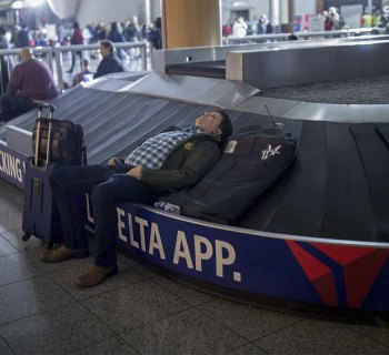 Delta Air Lines passenger asleep at baggage claim.