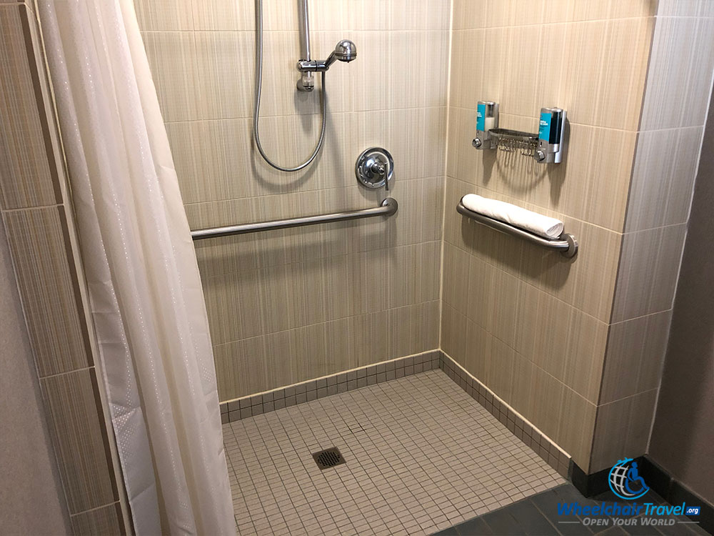Roll In Shower With Wall Mounted Soap Dispensers At An Aloft Hotel.