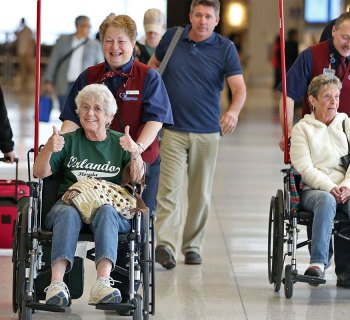 Passengers with reduced mobility being pushed in wheelchairs at the airport.