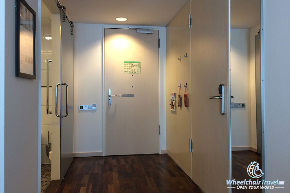 Interior corridor with accessible path to bathroom and full-length mirror.