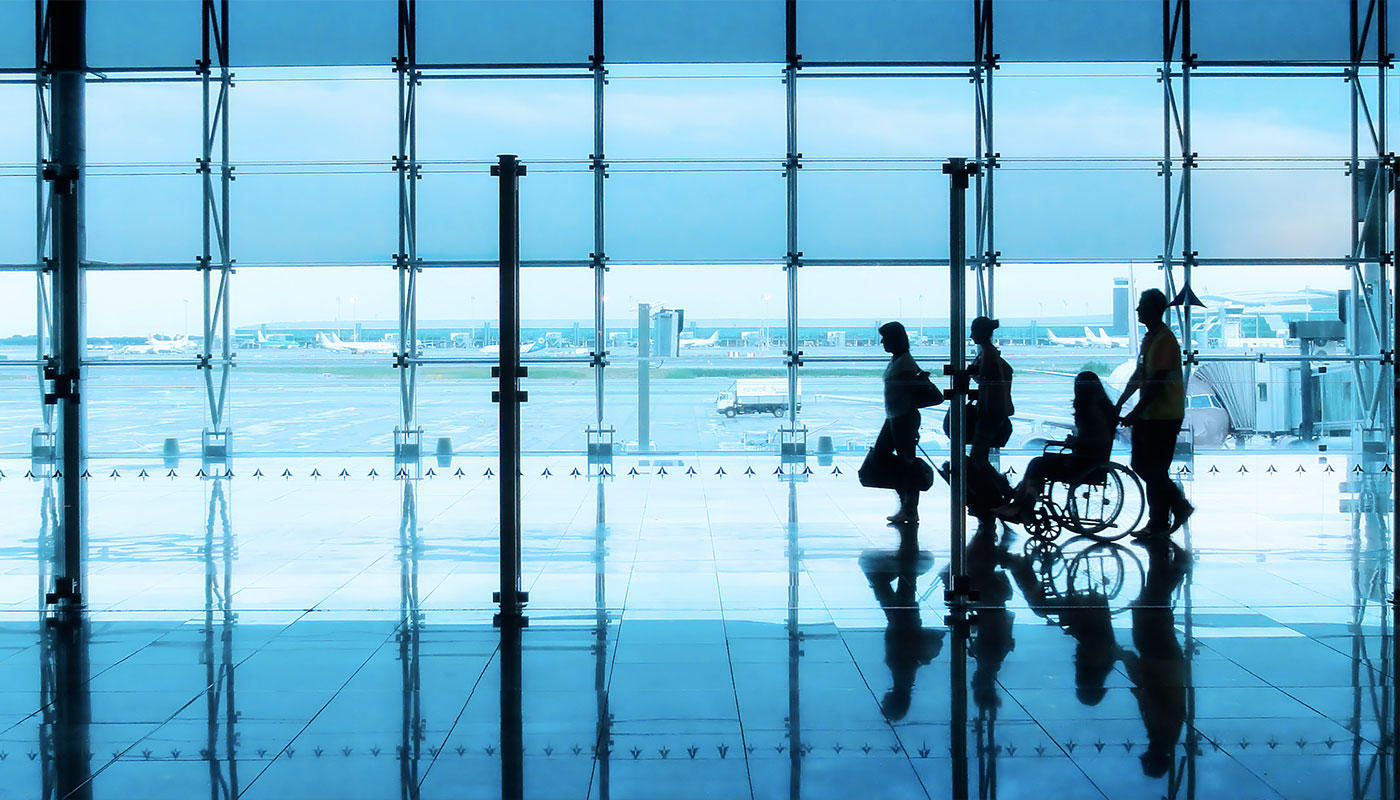 Airline passenger with a wheelchair in the airport terminal.