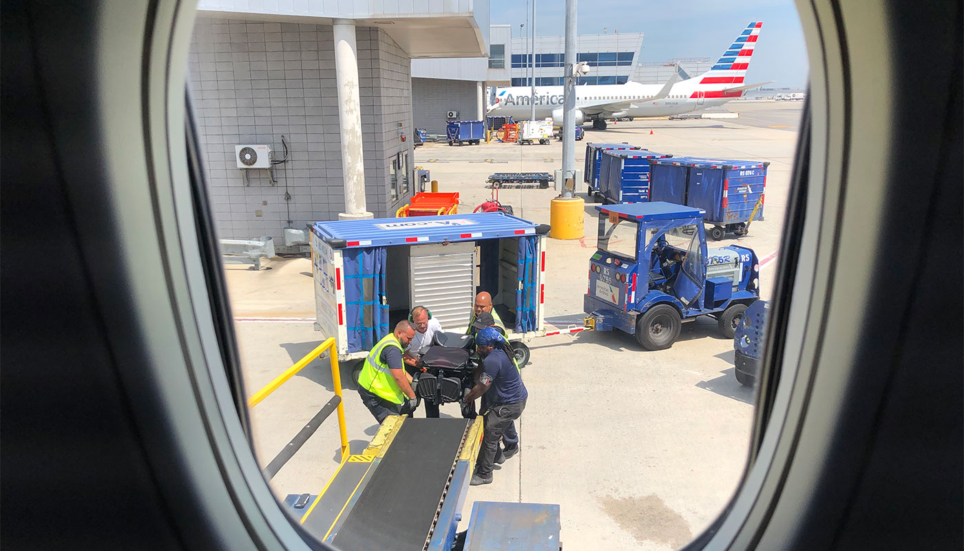 American Airlines baggage handlers lifting wheelchair at JFK Airport.