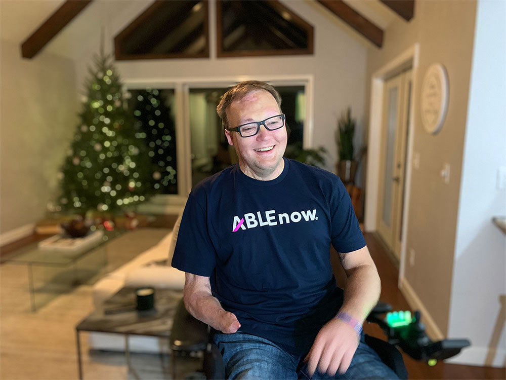 John pictured at home wearing an ABLEnow t-shirt.