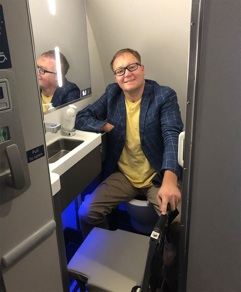 Wheelchair user seated in A220 lavatory.
