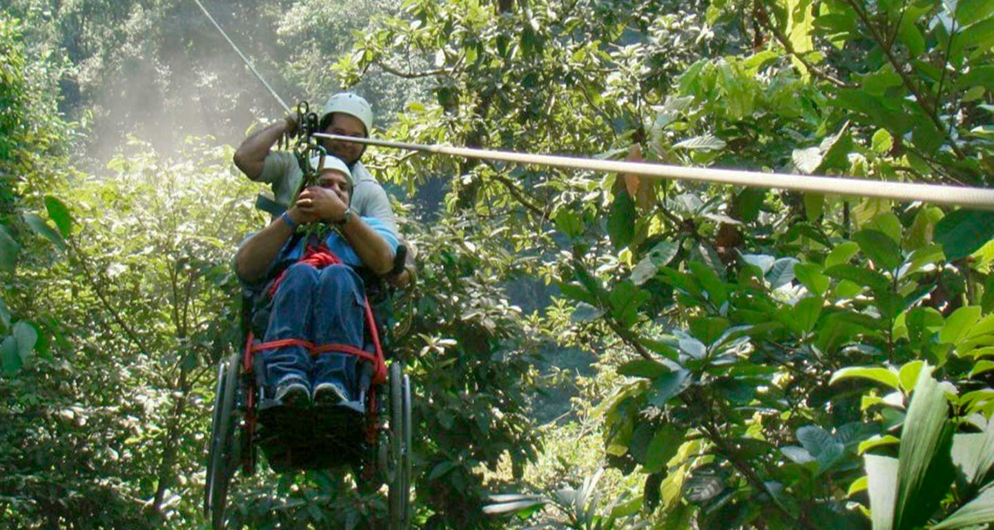 Person in wheelchair attached to zipline, going through forested area.