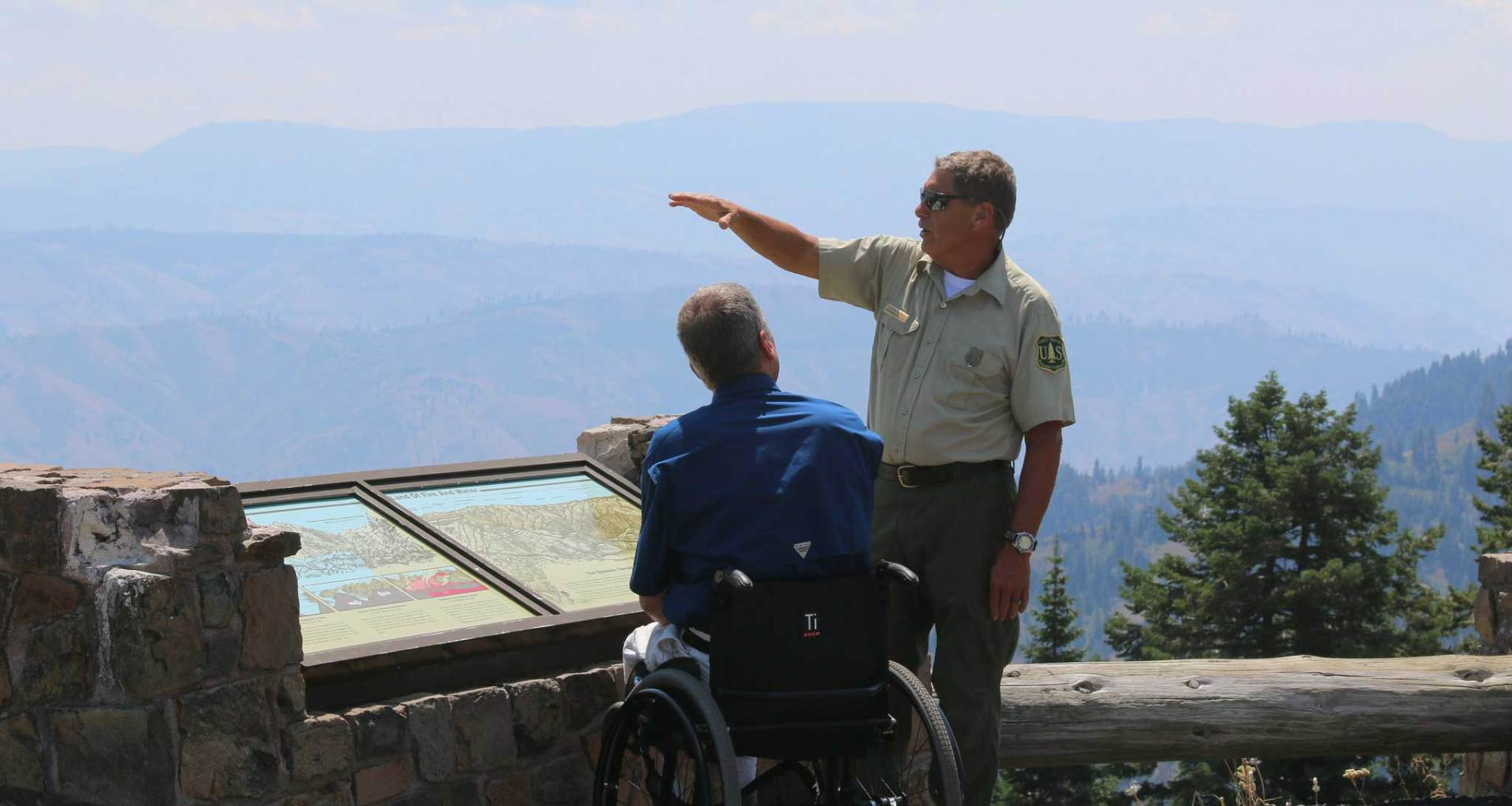 Park ranger speaking with a wheelchair user at an overlook inside a National Park.