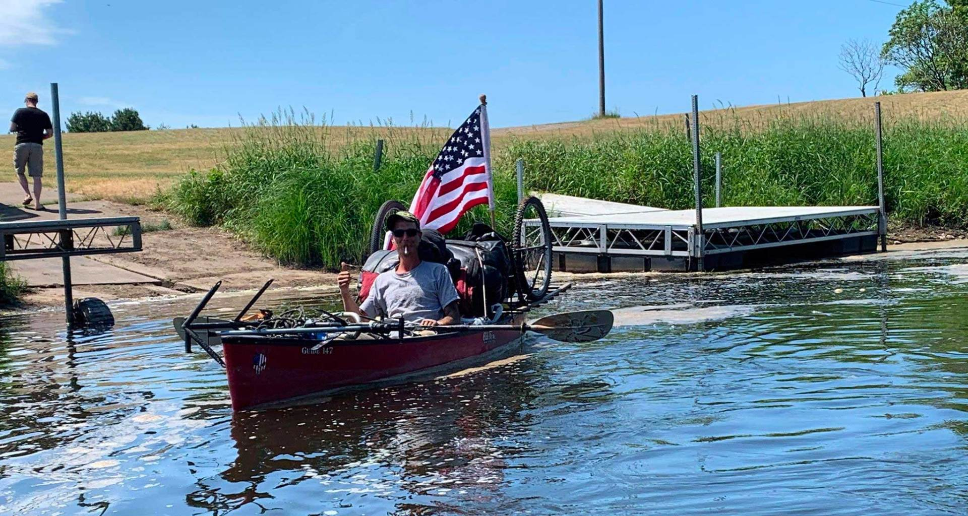 Man on canoe departing river launch point, with large American flag positioned at back of canoe.