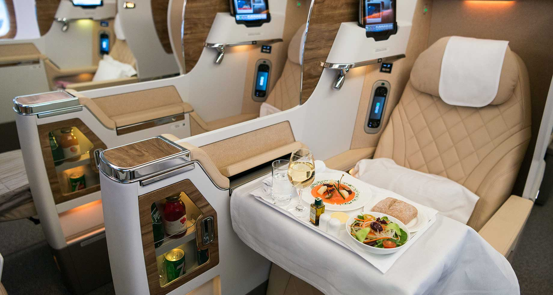 Emirates business class seat, with meal presented on tray table.