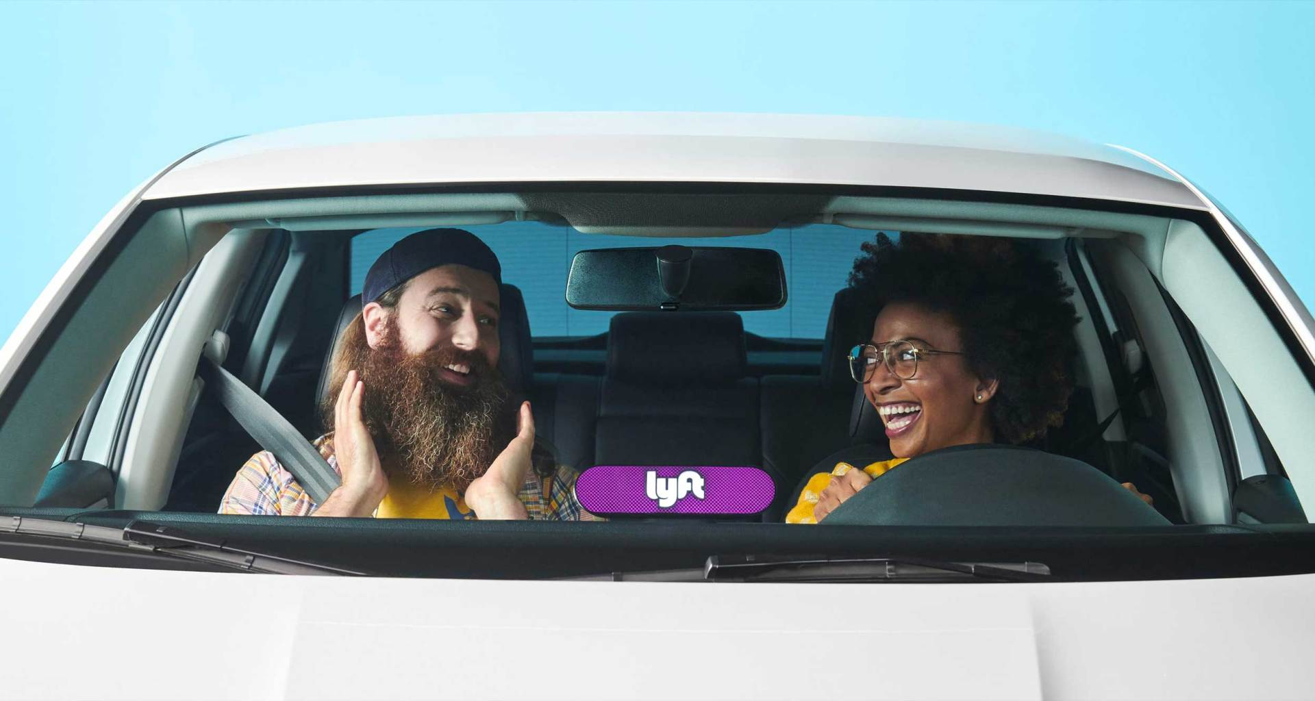 Man and woman in a white car with a illuminated Lyft sign in the window.