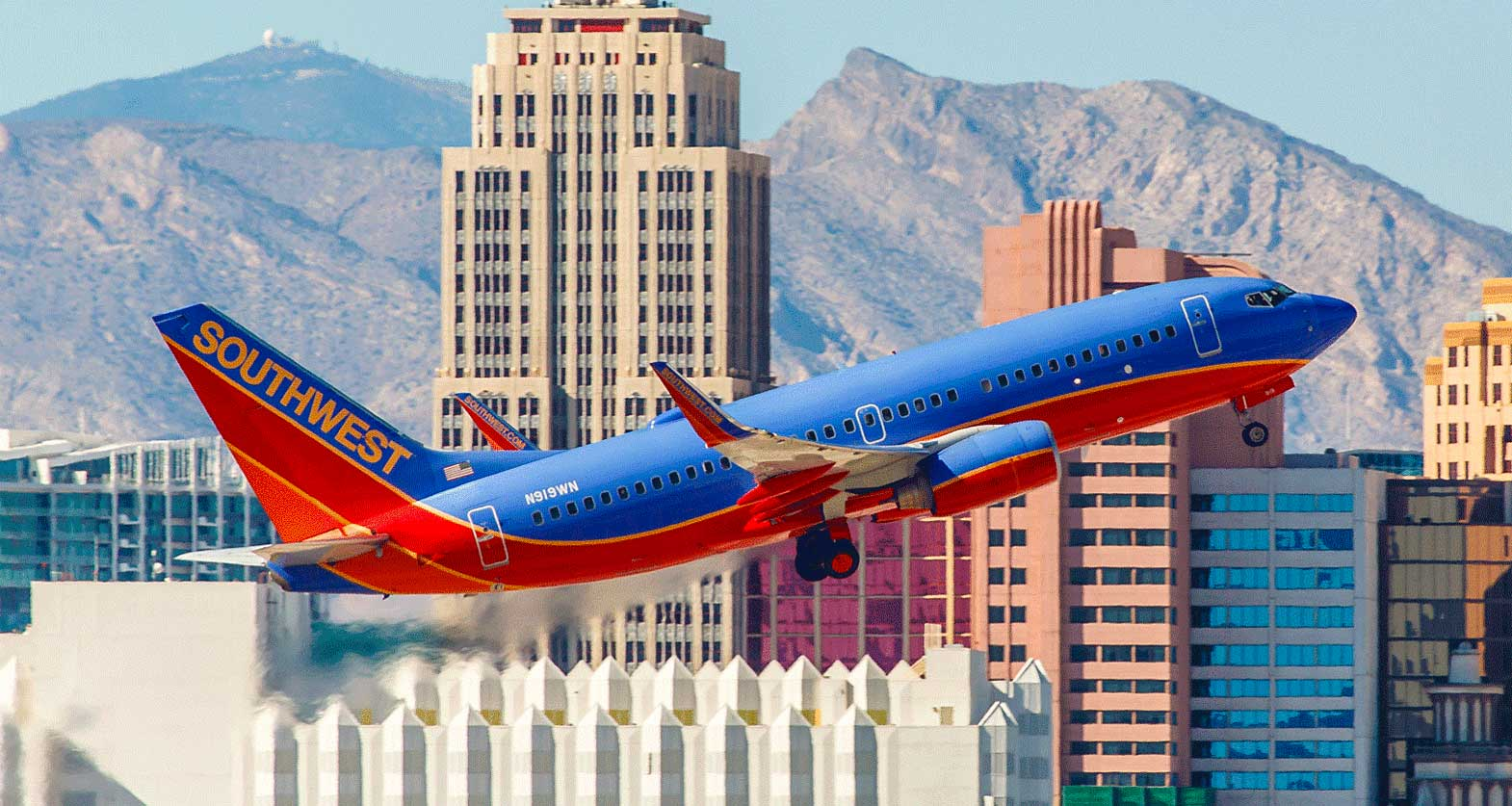 Southwest Airlines Boeing 737 inn takeoff climb; tall buildings in background.