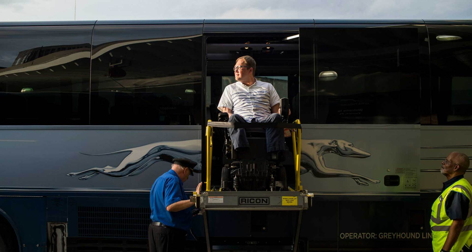 John Morris, seated in his wheelchair on the lift of a Greyhound Bus.