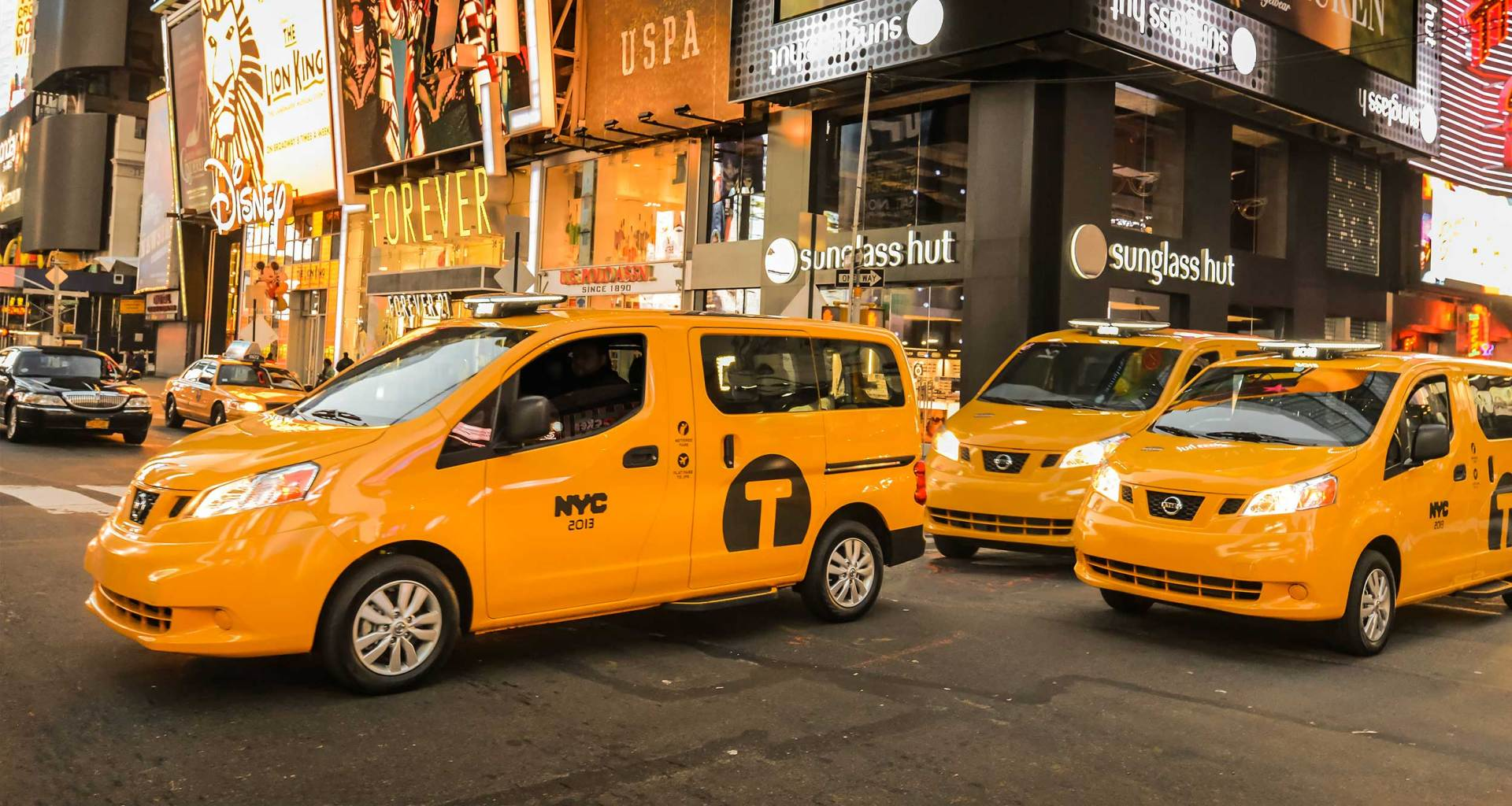 Wheelchair taxi vans on a street in New York City.