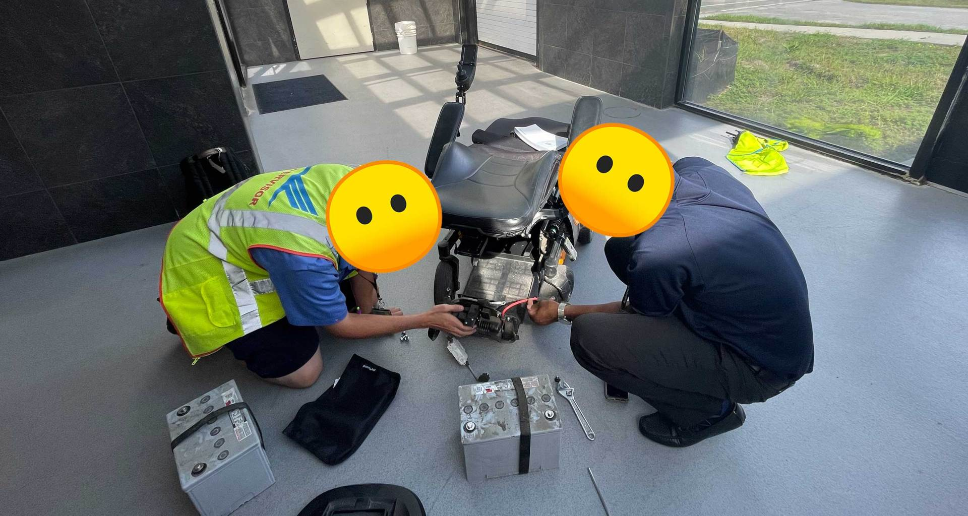 Two airline staff persons disassembling a power wheelchair with batteries removed.