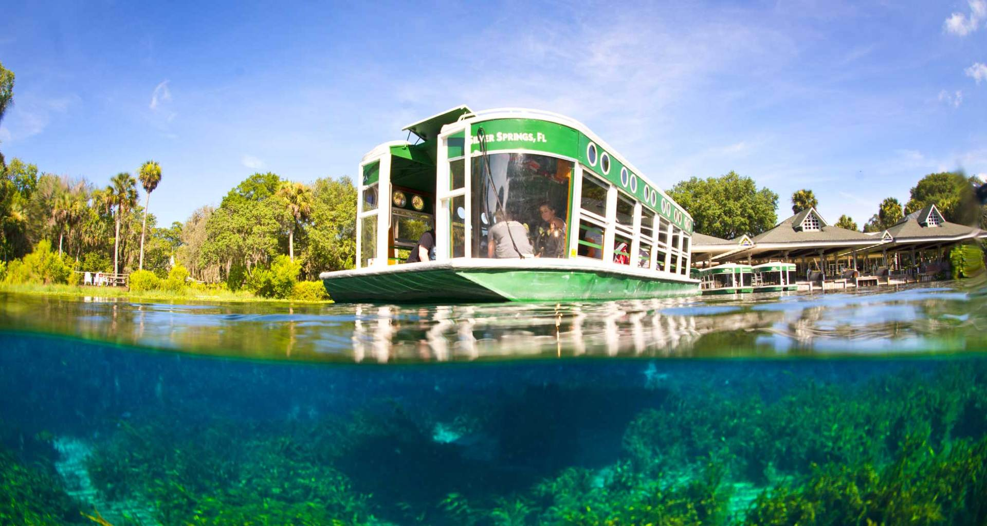 Glass bottom boat on river, with underwater view.