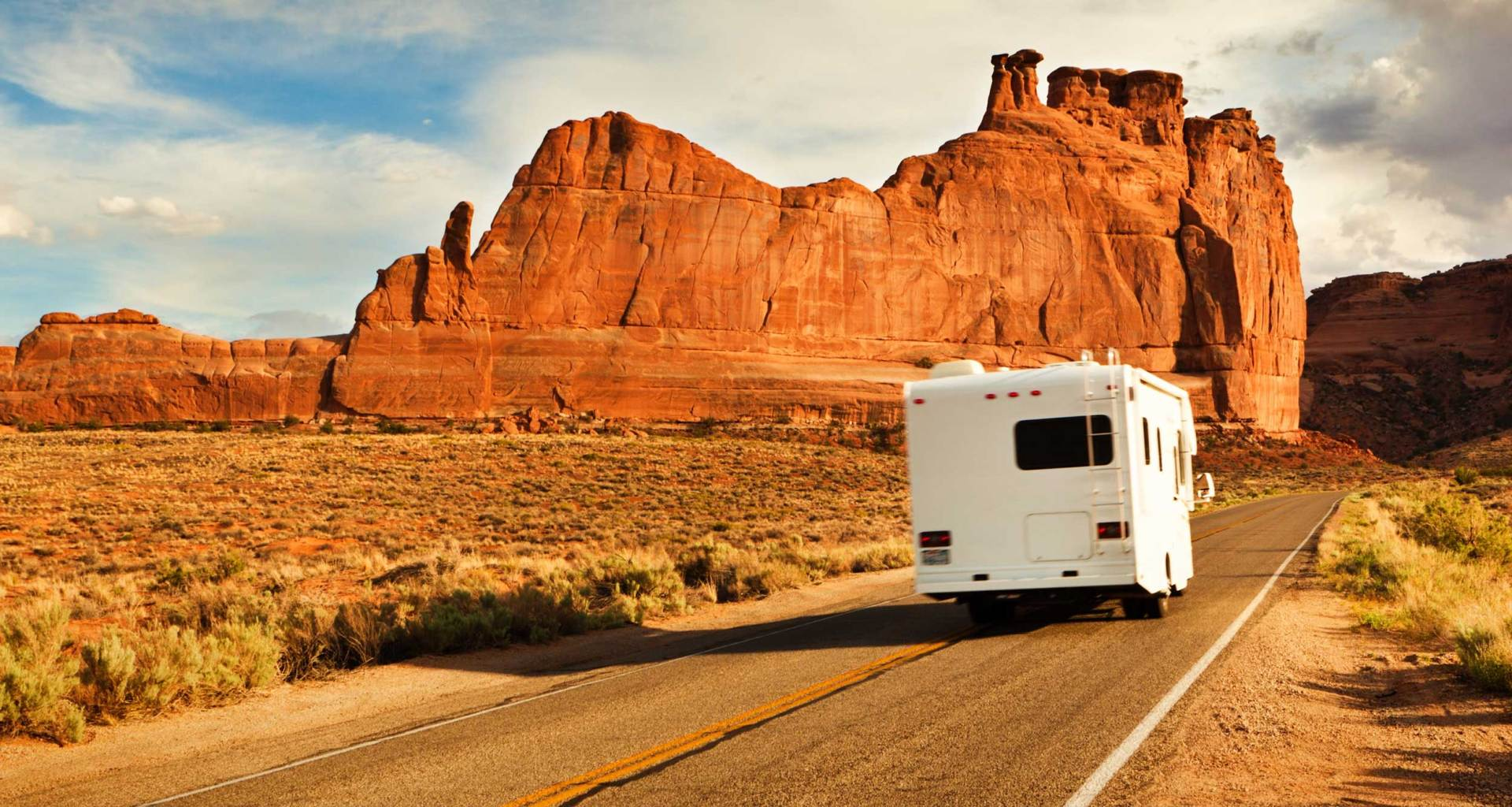 Wheelchair accessible RV driving down road.