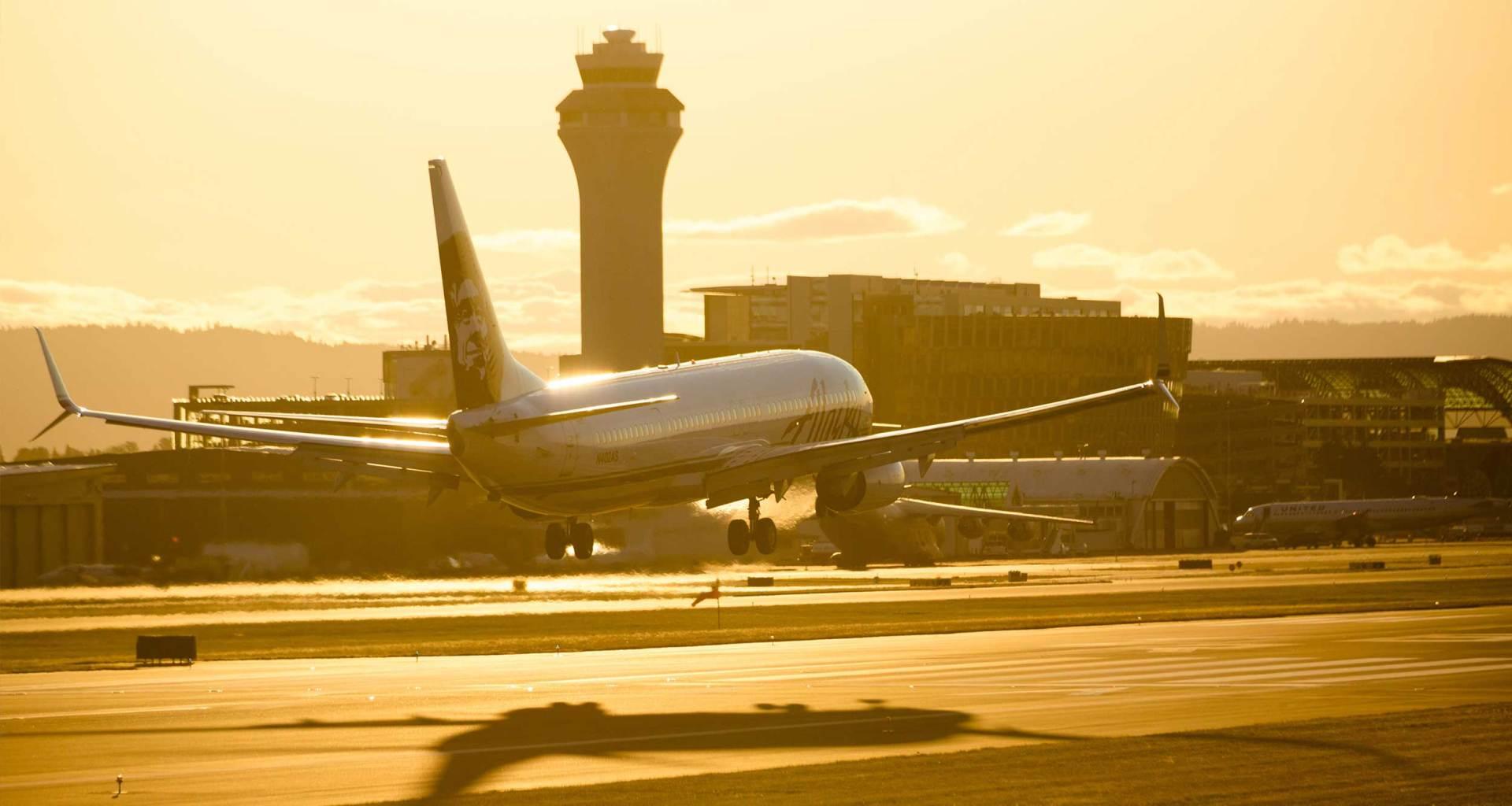 Alaska Airlines plane landing at sunset.