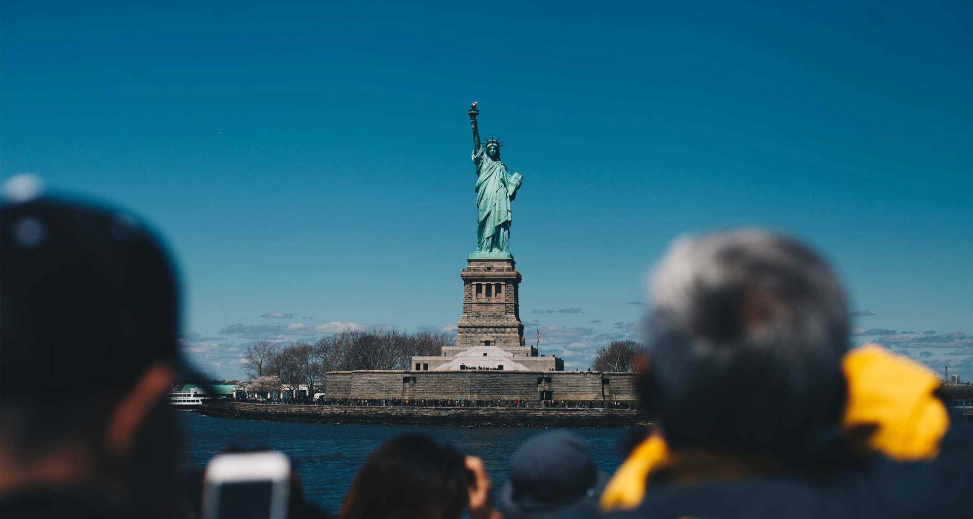 Crowd of people looking at and taking photos of the Statue of Liberty, seen on an island in the distance.
