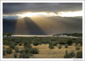 Rays of sun peek through on a dark, cloudy evening