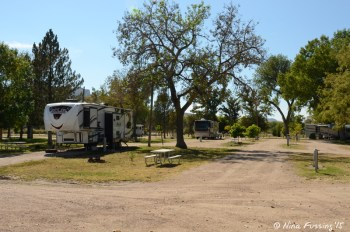 """Another site view. Empty site #16 on right with RV in #17. You can see us in the back in #4. Site #16 has one of the bigger """"sitting areas"""" in the park."""
