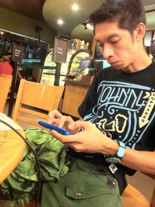 My brother, King, playing on his phone at Starbucks (Fully Booked)