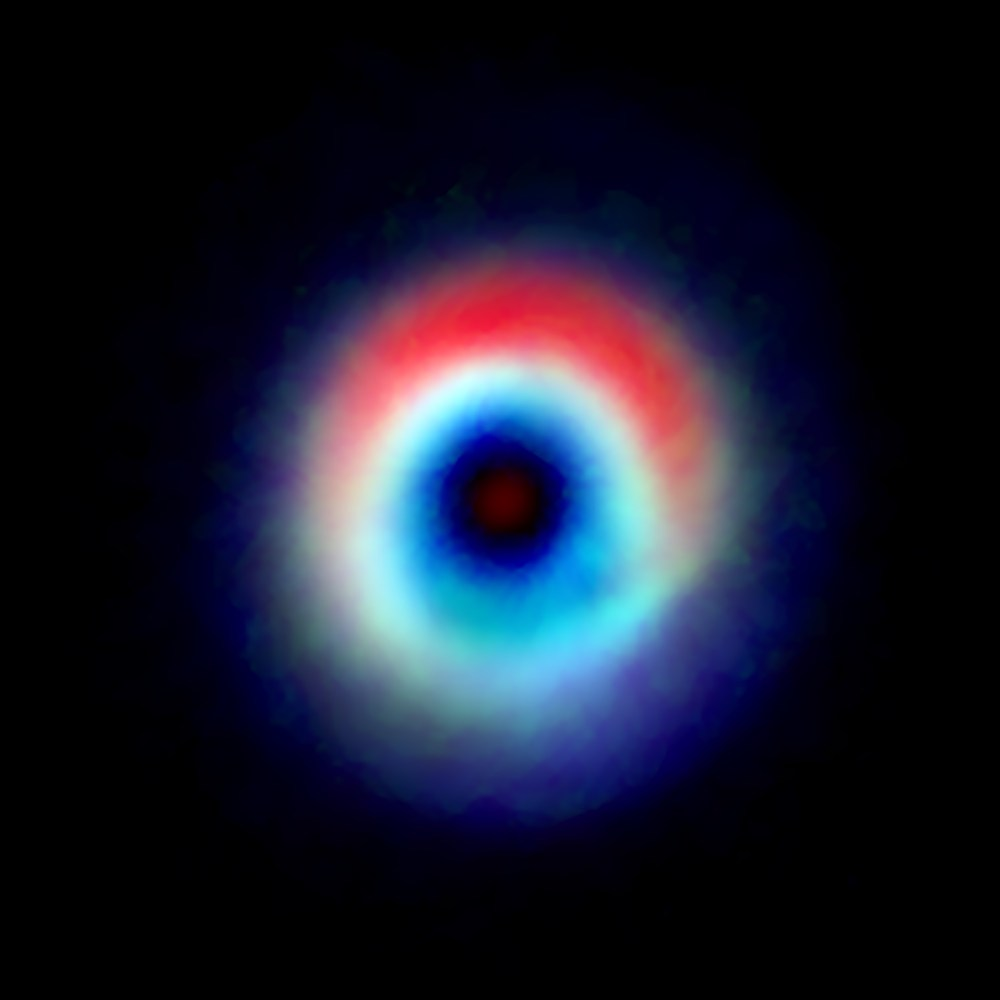 """A composite image of the HD 142527 binary star system from data captured by the Atacama Large Millimeter/submillimeter Array shows a distinctive arc of dust (red) and a ring of carbon monoxide (blue and green). The red arc is free of gas, suggesting the carbon monoxide has """"frozen out,"""" forming a layer of frost on the dust grains in that region. Astronomers speculate this frost provides a boost to planet formation. (National Radio Observatory)"""