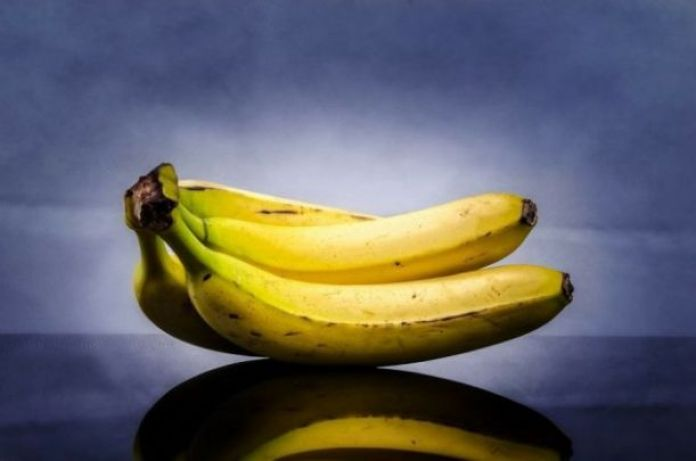 A close-up of ripe bananas on a blue background