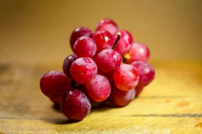 A bunch of red grapes rest on a wooden surface