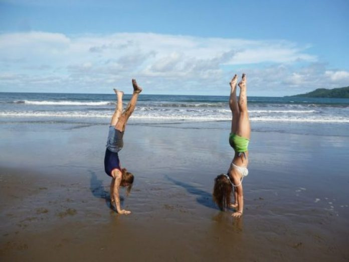 Two women, doing cartwheels on a sandy beach, are getting fit for the summer