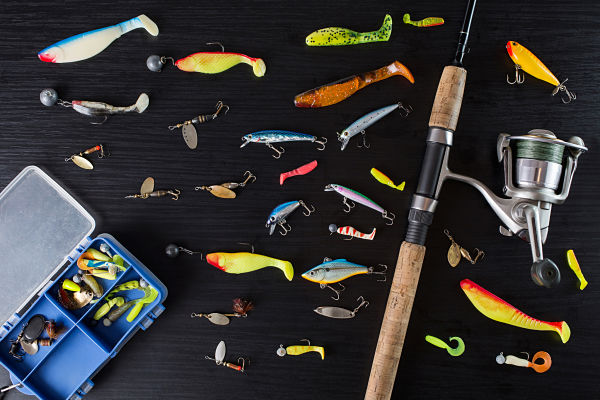 Fishing gear on a dark table. Spoon-baits wobblers multicolored bait for fish on the table. Fishing rod and coil on a black surface. Box for baits. Fishing reel, fishing lures. Go fishing. Fishing tackle. Fishing Rod