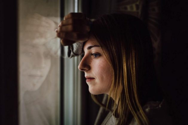 Woman looks out window and wonders if CBD for anxiety relief is real
