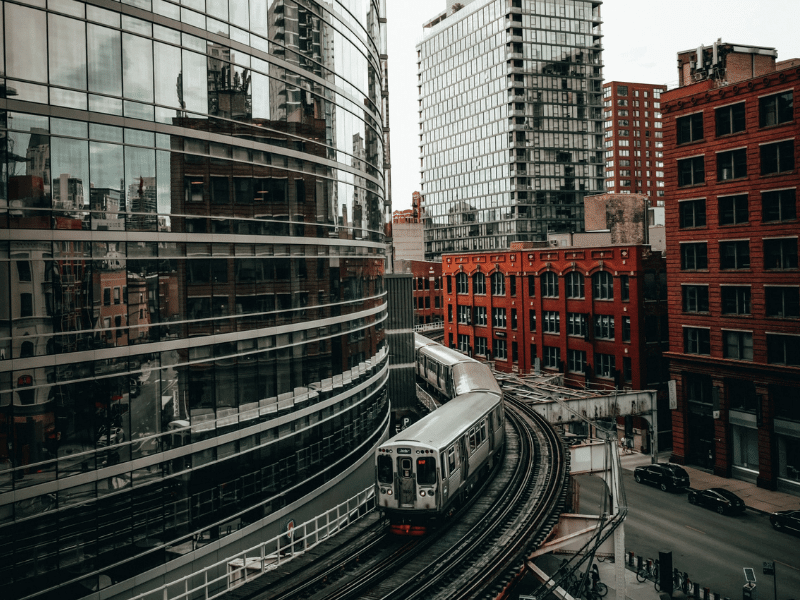 An aerial view of a train passing by on West Kinzie Street in Chicago. The city is reflected in a nearby building's windows.