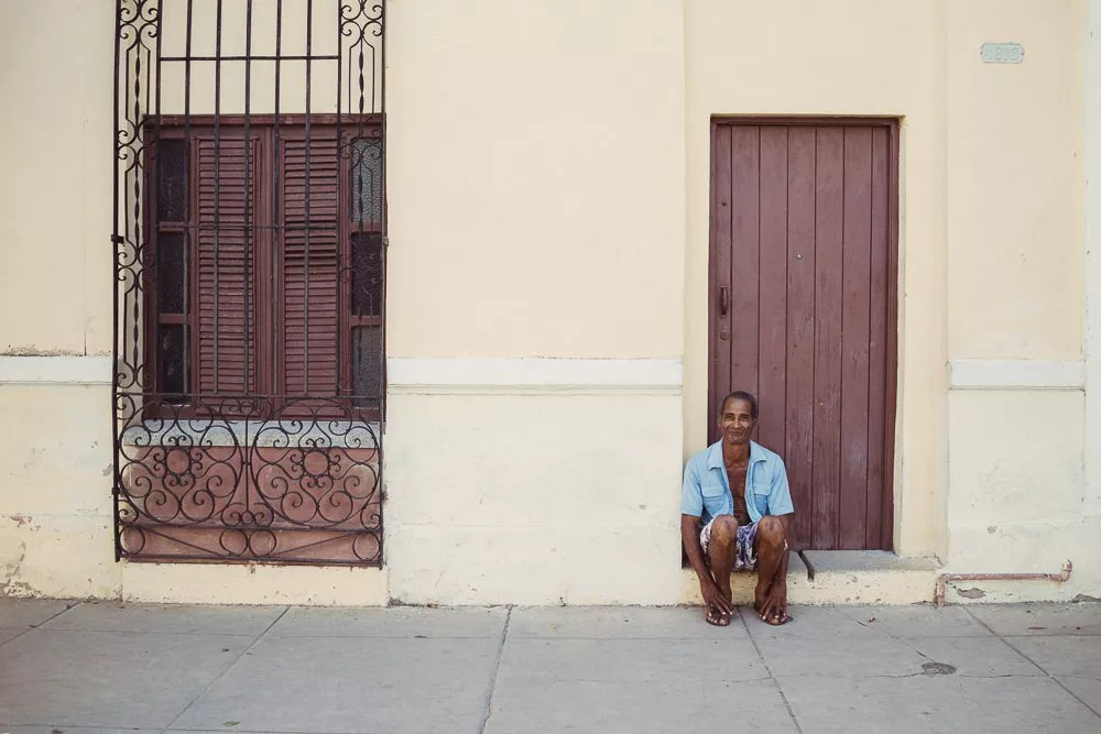 Portrait of Cuban man sitting on street smiling in Cienfuegos