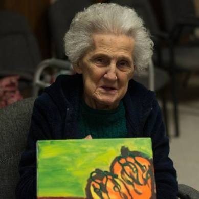 elderly woman holding up her pumpkin painting