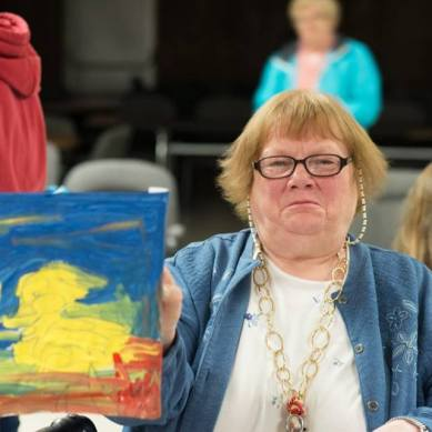 elderly woman holding up her painting