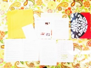papers laid out on a yellow bedspread