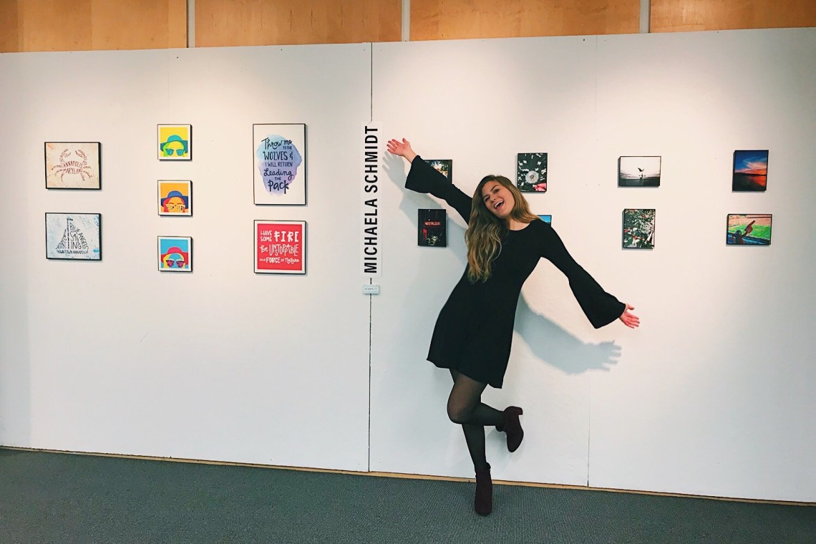 girl standing in front of pieces of art