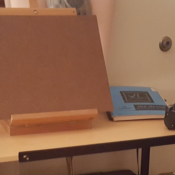 a desk with a camera, sketchbook, and table easel