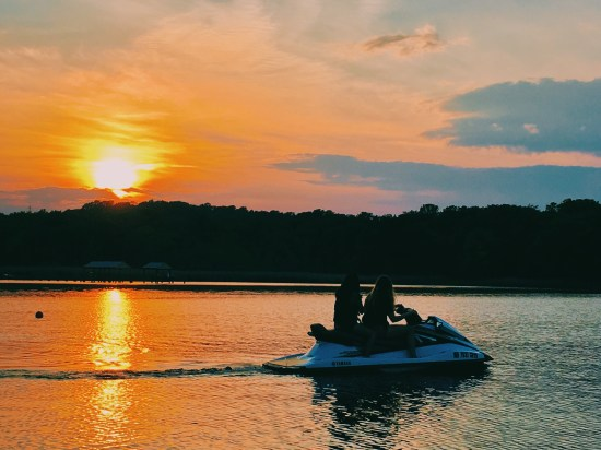 Orange sunset with two girls on a jetski