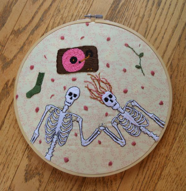 Embroidered skeleton couple with black outline lying on the floor listening to pink vinyl record