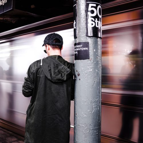 Brooklyn NY features a man standing outside a subway.