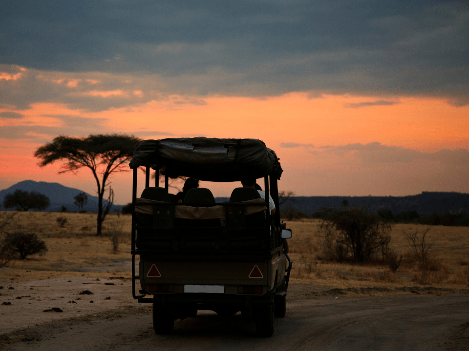 A safari jeep in the African sunset on the horizon