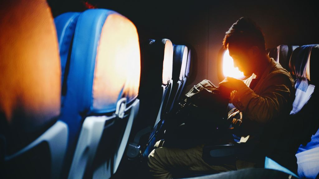 first time flying - man looking in his bag sitting on an airplane as the sun comes through the window